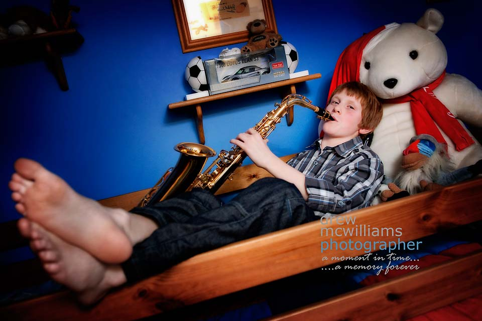 Young boy lying on bed playing clarinet