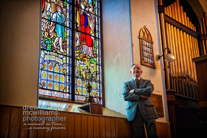 Ernie Martin in Dromore Non-subscribing Church beside one of the stained glass windows